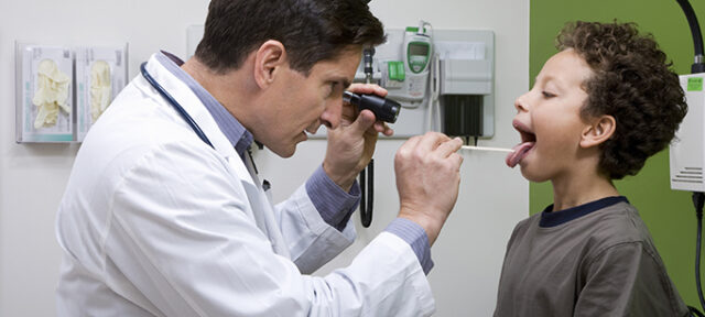Pediatric Doctor Looking In Patient's Mouth