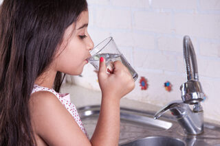 Little girl drinking water from kitchen faucet
