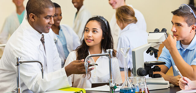 photo - High School Science Teacher Talking with Students in Chemistry Lab