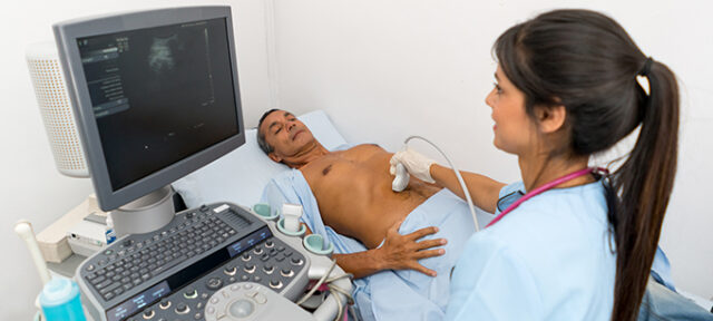 Radiologist doing a sonogram at the hospital on a male patient - medical exam