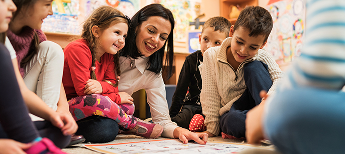 Happy teacher with a group of kids in a preschool.