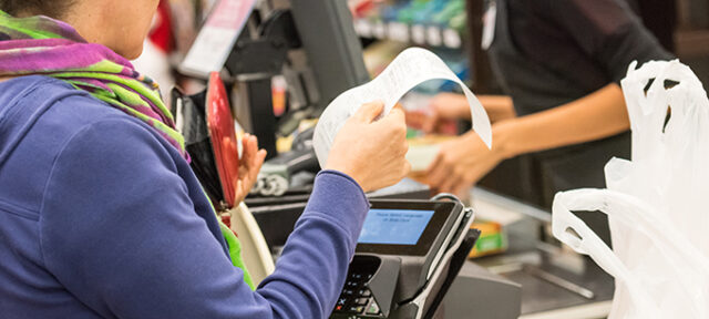 Woman electronic signing her bill at the supermarket
