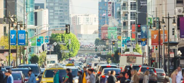 Horizontal color image of the famous 5th Street of San Francisco with pedestrians, cityscape and traffic seen from Market Street. Letterbox format. Copy space above.