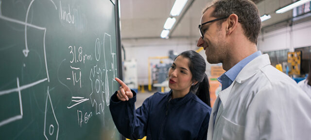 Portrait of a female engineering student talking to her teacher trying to solve a problem on the board - education concepts