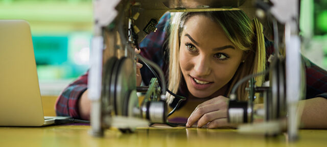 Young happy woman working on innovative robot in laboratory. Copy space.