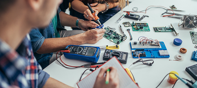 Group of students engineers working on a computer part
