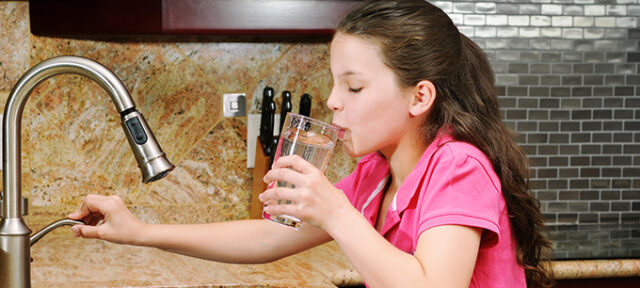 A Little Girl Getting A Glass Of Water
