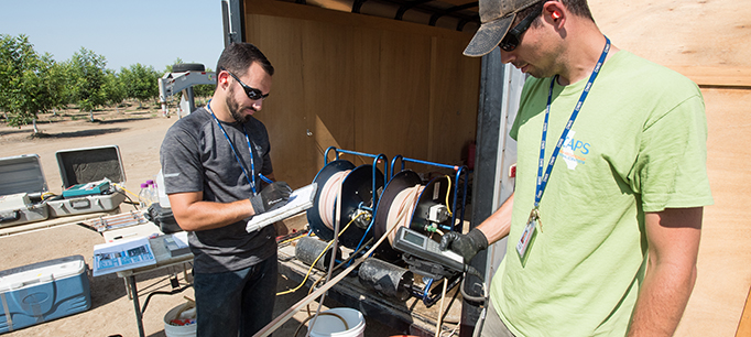 Fish and Wildlife Scientific Aid Brian Bettencourt (left) records data while Environmental Scientist Evan MacKinnon (right) reads off water quality parameters from a multi-parameter water quality meter at a well in Sutter County, California for the Department of Water Resources