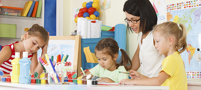 Children With Teacher Draw In The Classroom