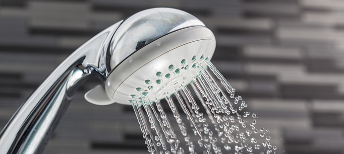 Shower Head With Water Drops Falling On A Bathroom