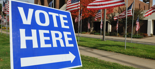 Vote Here Sign And American Flags