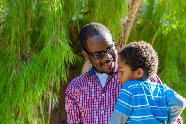 photo - African American father holding young son