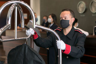 photo - Bellboy Working at a Hotel, Wearing a Mask