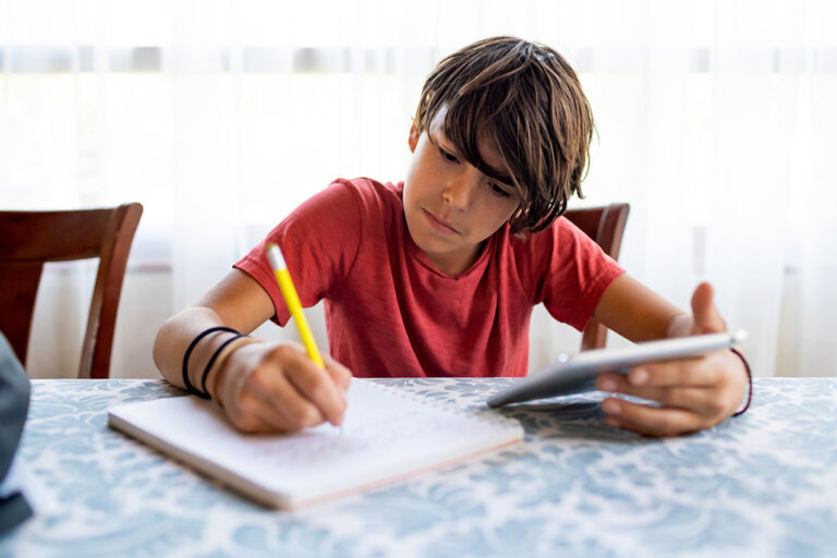 photo - Boy Doing Schol Work from Home with Pen, Paper, and Tablet