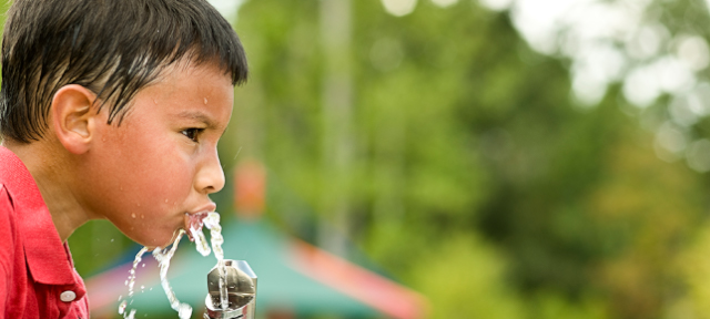 Boy Drinking From Water Fountain on Hot Day