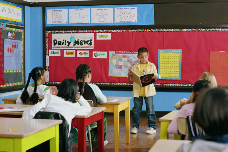 photo - Boy Reading in Front of Class