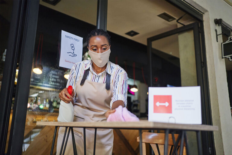 photo - Cafeteria Worker Wearing Mask and Cleaning Outside Table