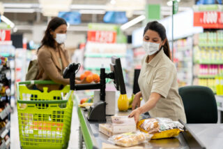 photo - Cashier Scanning Products at a Grocery Store Wearing a Mask