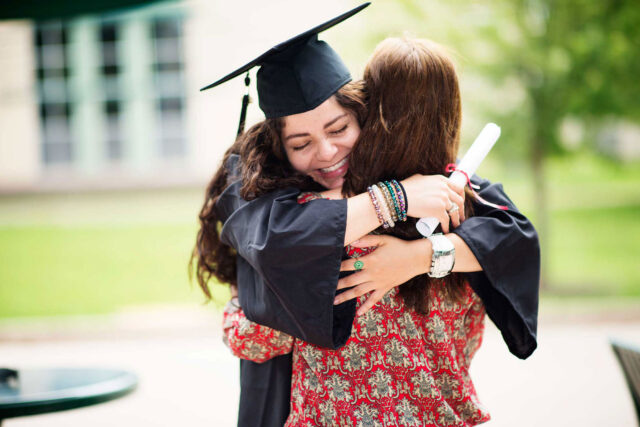photo - College Graduate Hugging Mother and Holding Diploma