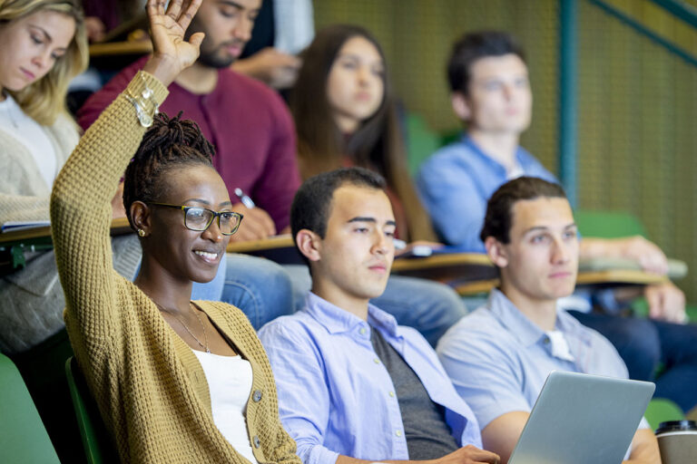 photo - college student raising hand in lecture class