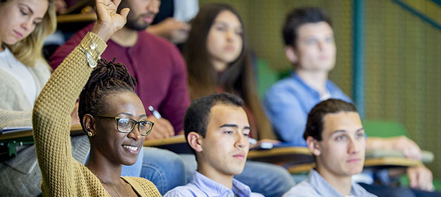photo - College Student Raising Hand in Lecture Classroom