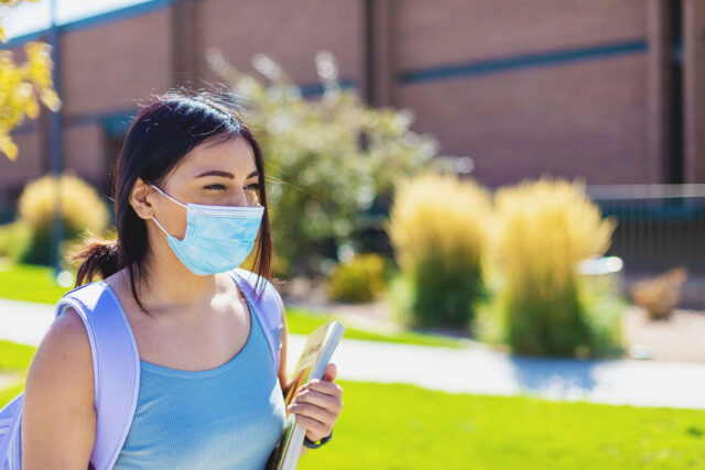 photo - College Student Walking on Campus and Wearing a Mask
