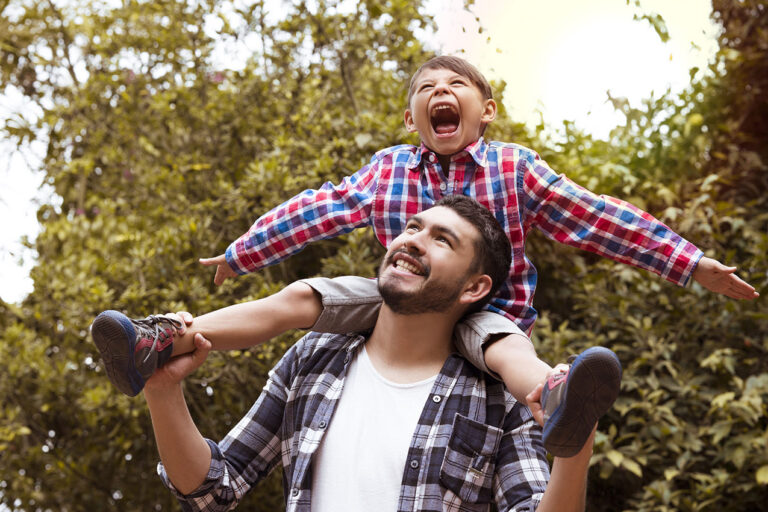 photo - Dad Carrying Son on His Shoulders in Park