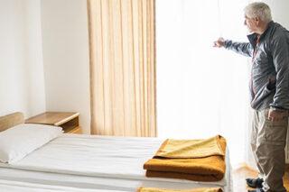 photo - Elderly Man in Hotel Room