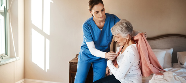 Photo of an elderly woman getting help from a caregiver in a nursing home