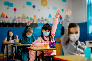 photo - Elementary School Students Raising Hands and Wearing Masks in Classroom