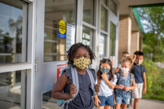 photo - Elementary School Students Wearing Masks and Standing in a Line Outside of School