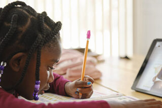 photo - An Elementary School Student Working at Home, Using a Tablet
