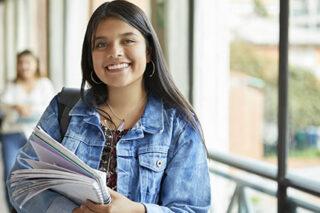 photo - Female College Student Holding Notebook in Unversity Corridor