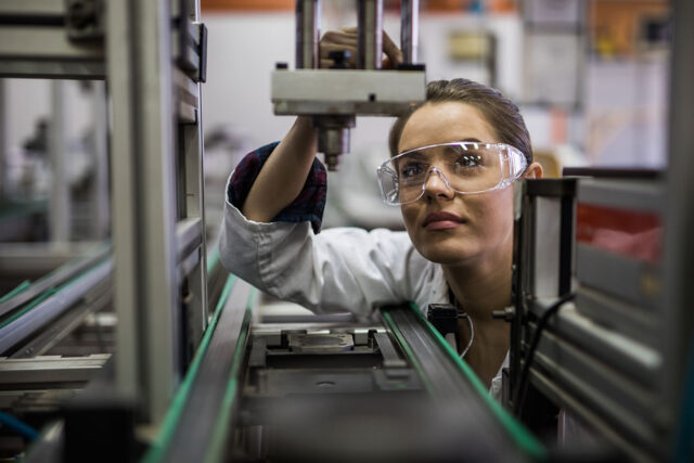 photo - Female Engineer Examining a Machine