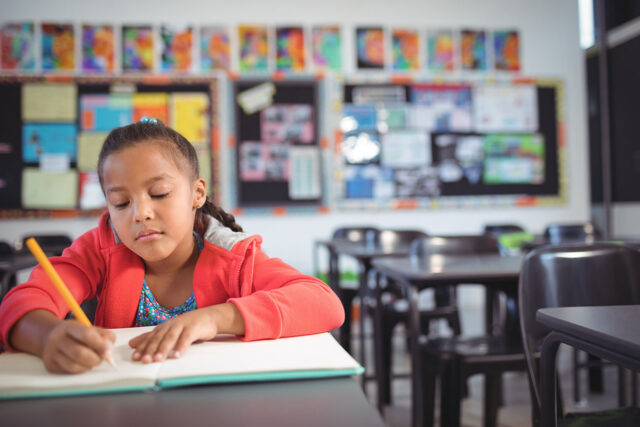 photo - Girl Writing While Sitting at Desk in Classroom