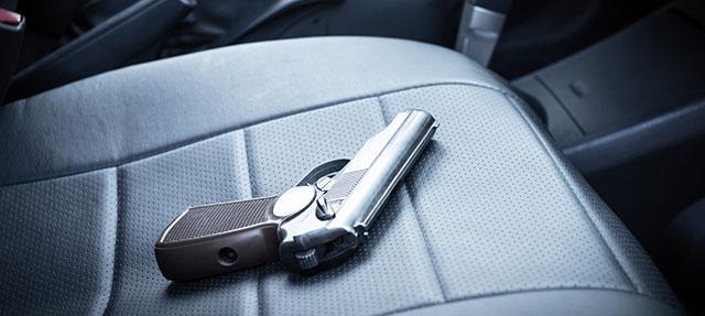 photo - Gun Sitting On Front Seat of Car