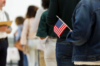 photo - Handheld US Flag and People Standing in Line