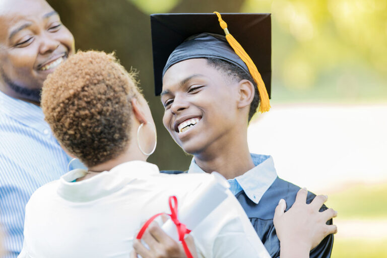 photo - High School Graduate Smiling and Hugging Mother After Graduation Ceremony