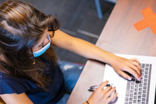 photo - High School Student Wearing Mask and Taking Test on Lap Top