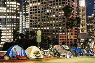 photo - Homelss Tents Beside Skyscrapers in Los Angeles Downtown at Night