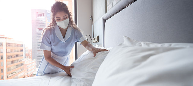 photo - Hotel Maid Making Bed and Wearing Mask