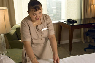 photo - Maid Making Bed In Hotel