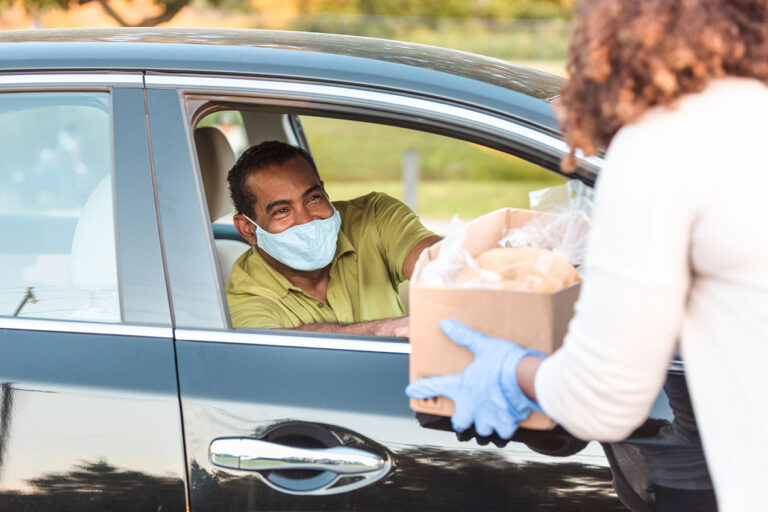 photo - Man in Car Wears Mask While Receiving Box of Food