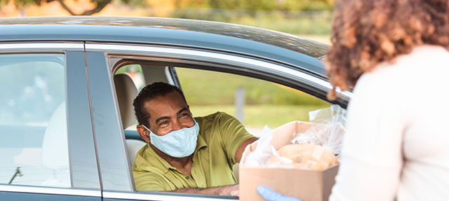 photo - Man in Car Wearing Mask and Picking Up Box of Food