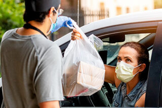 photo - Masked Woman in Car Picking Up Meals