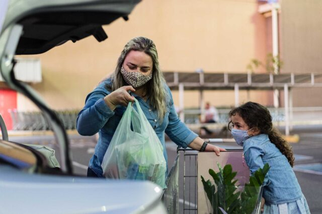 photo - Mom With Daughter Putting Groceries In Car