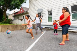 photo - Mother and Children Playing Ball Outdoors