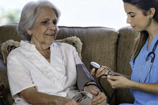 photo - Nursing Home AssistanceTaking Blood Pressure of Senior Woman