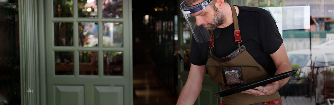 photo - Restaurant employee clearing tables with a face mask