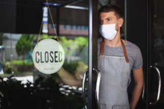 photo - Restaurant Worker Wearing Mask and Hanging Closed Sign on Door